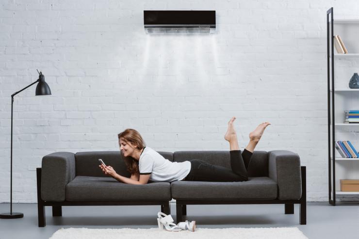 Frau auf Sofa unter Klimaanlage